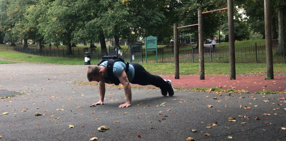 Performing push-ups while wearing the Gravity Fitness Weighted Vest