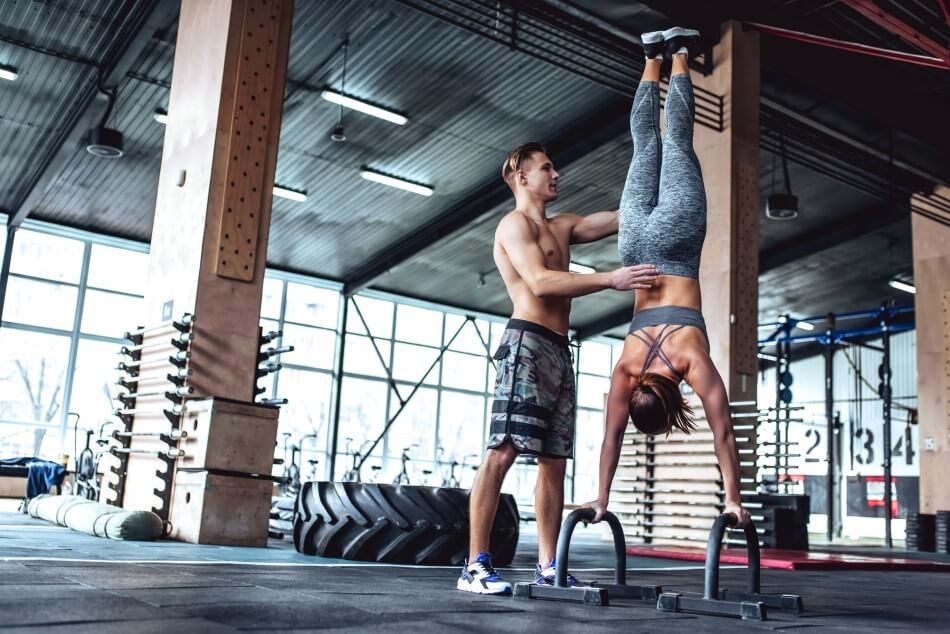 Woman performing handstand with spotter