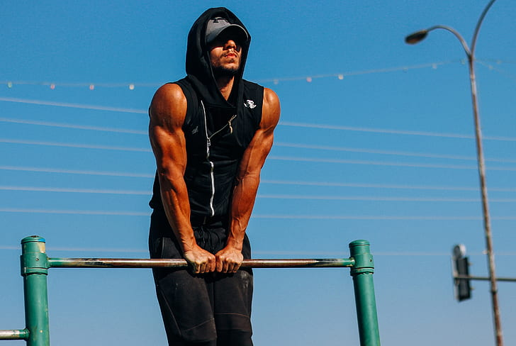 Man showing muscular arms while performing straight bar dips