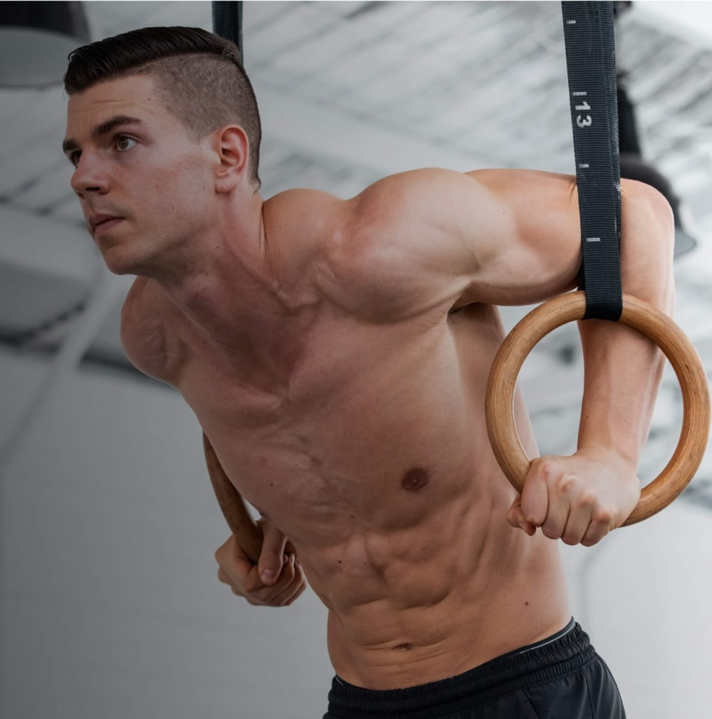 Daniel Vadnal (Fitness FAQs) performing dips on wooden gymnastic rings