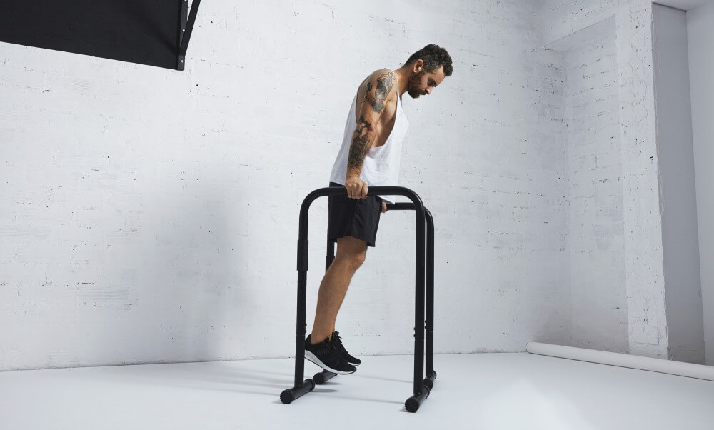 Athlete performing dips on a dip bar (stock photo)