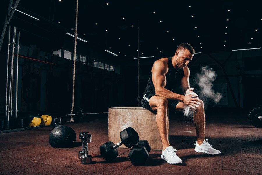 Man resting on a box in the gym