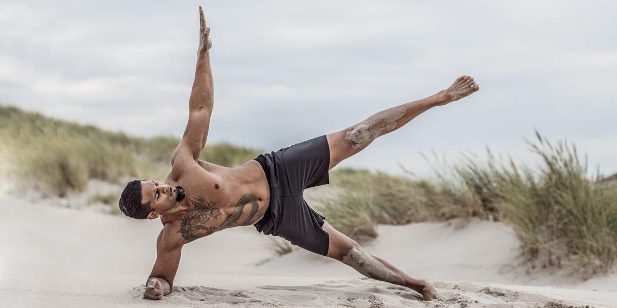 Man performing Yoga on the beach